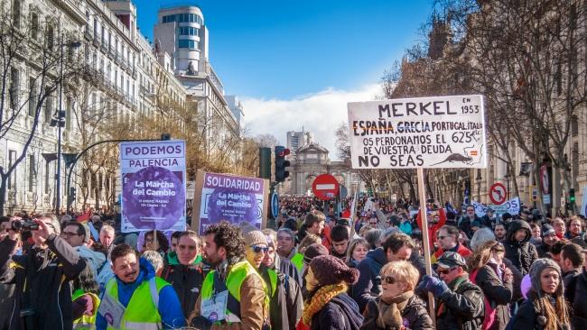 """Manifestación del partido Podemos en Madrid, """"La marcha del cambio"""". Vista de la calle de Alcalá desde Cibeles. La pancarta reza: """"Merkel, en 1953 España, Grecia, Portugal, Italia, etc. os perdonamos el 625% de vuestra deuda. No seas """""""